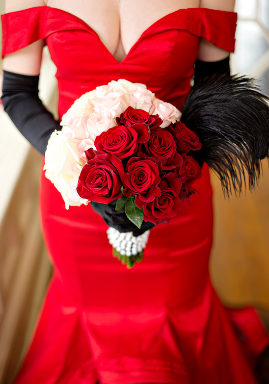 red and white rose bouquet with black feathers