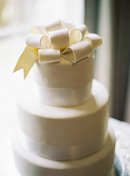 white wedding cake with bow on top
