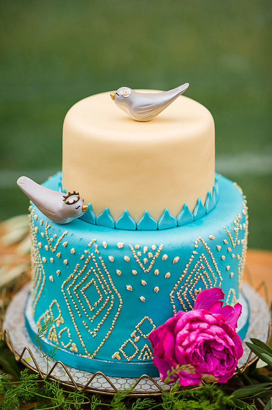 blue and gold wedding cake with bird toppers