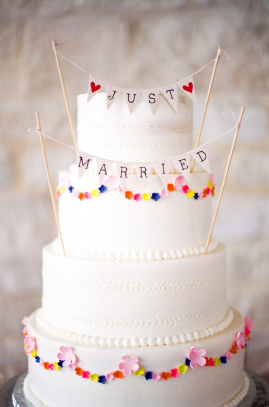 mini bunting topped wedding cake @weddingchicks