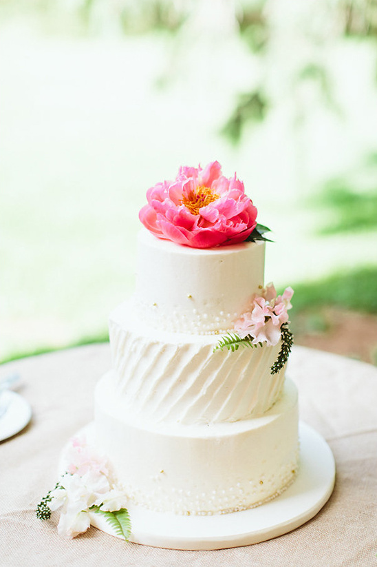 white wedding cake with peony topper @weddingchicks