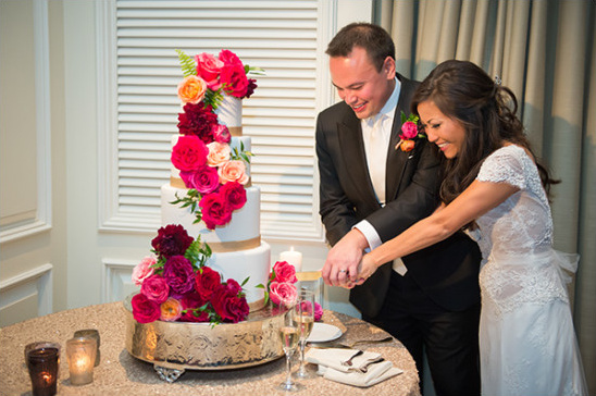 Four tier wedding cake with cascading pink flowers