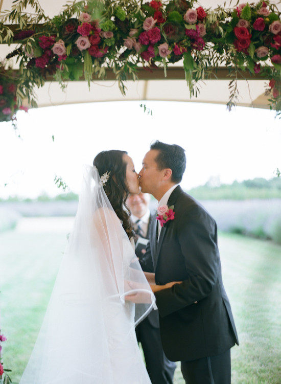 kissing under a purple rose wedding arch