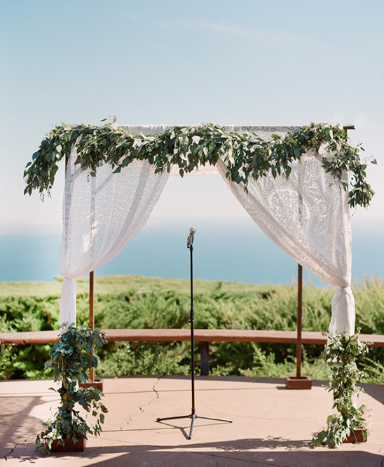 Seaside wedding arch with green garland