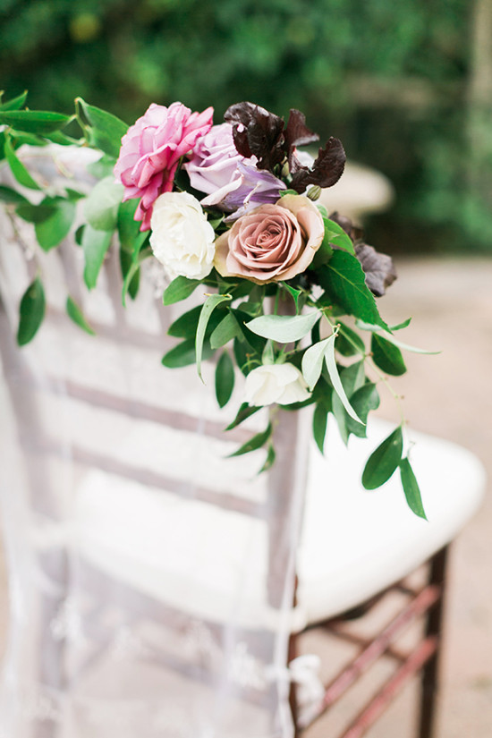 flower drapped wedding chairs