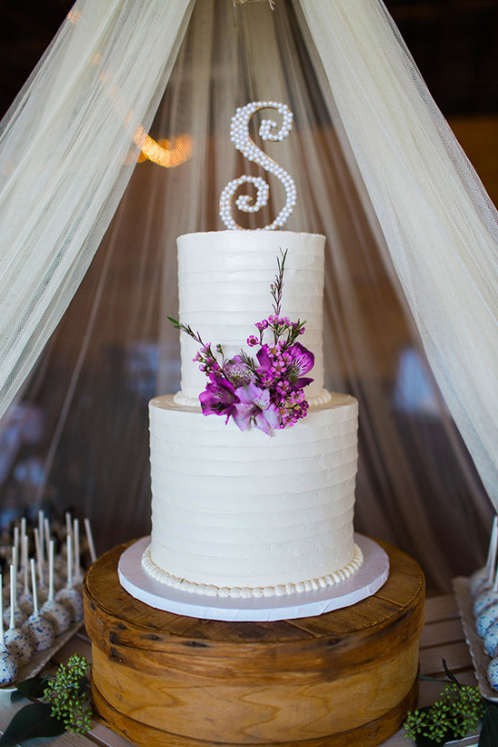 classic white wedding cake with purple flowers and initial topper