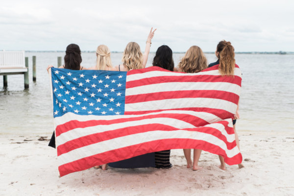 bachelorettes on the beach with flag