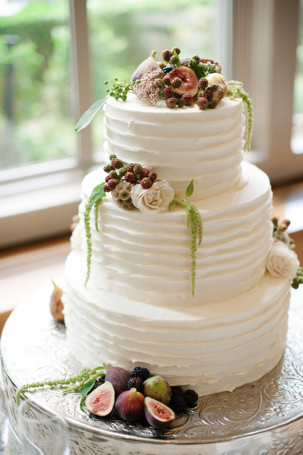 white wedding cake with draped florals