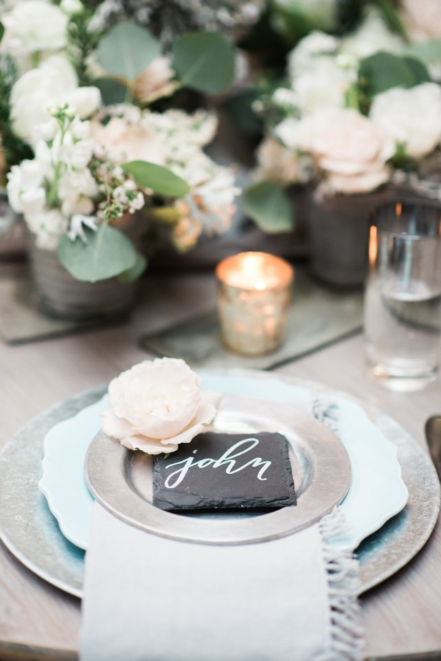 silver and blue place setting with slate place card