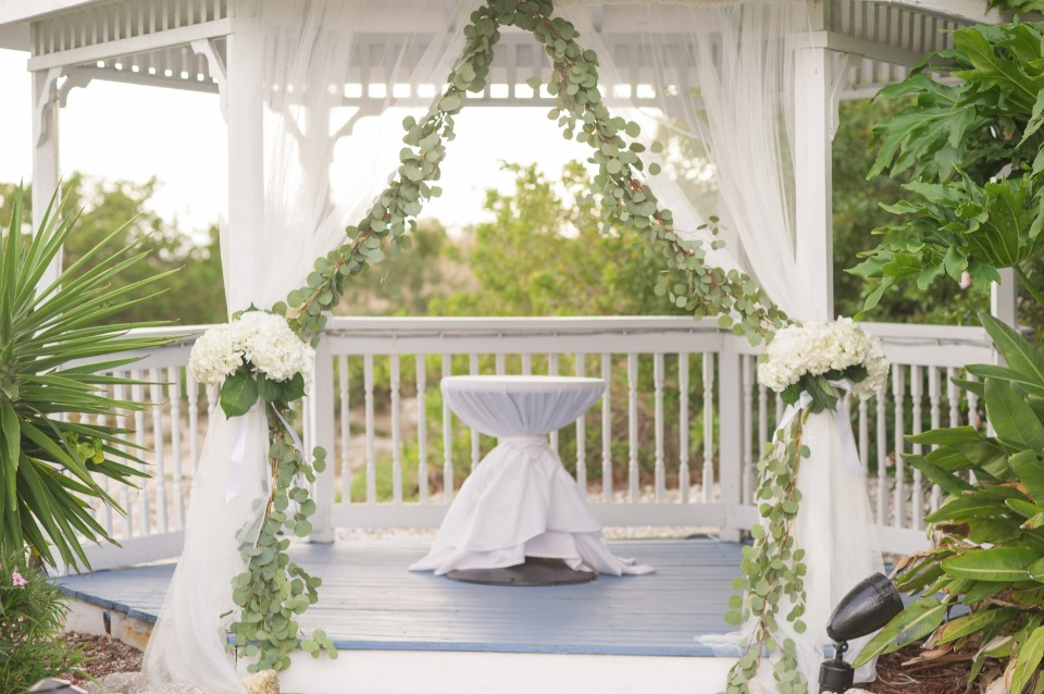 wedding gazebo with greenery garland and florals