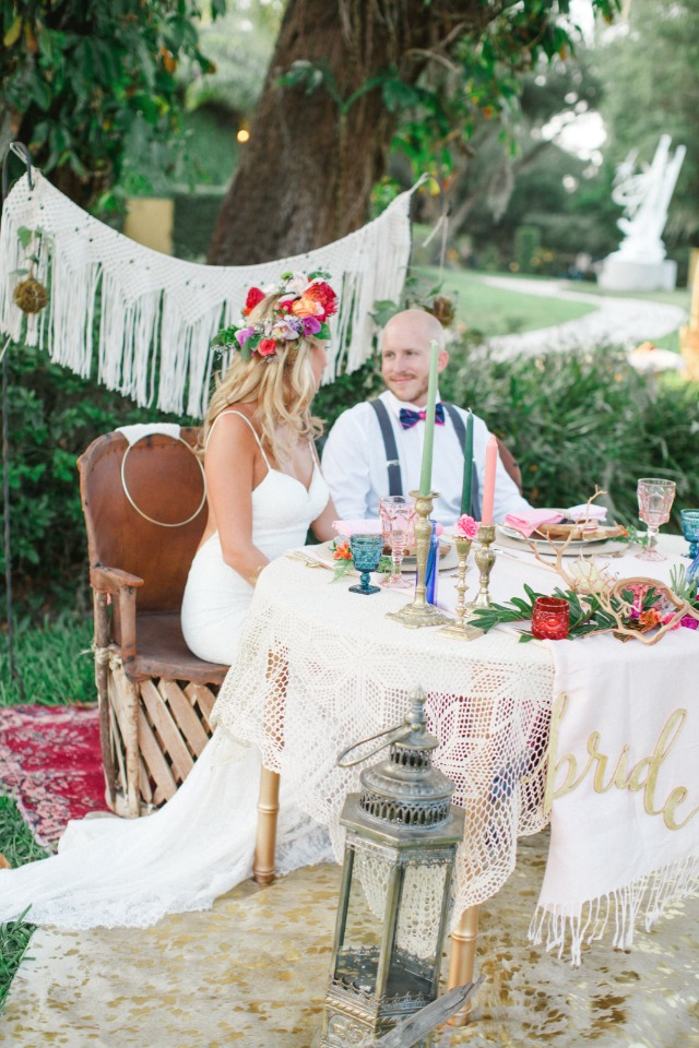 bride and groom at boho sweetheart table
