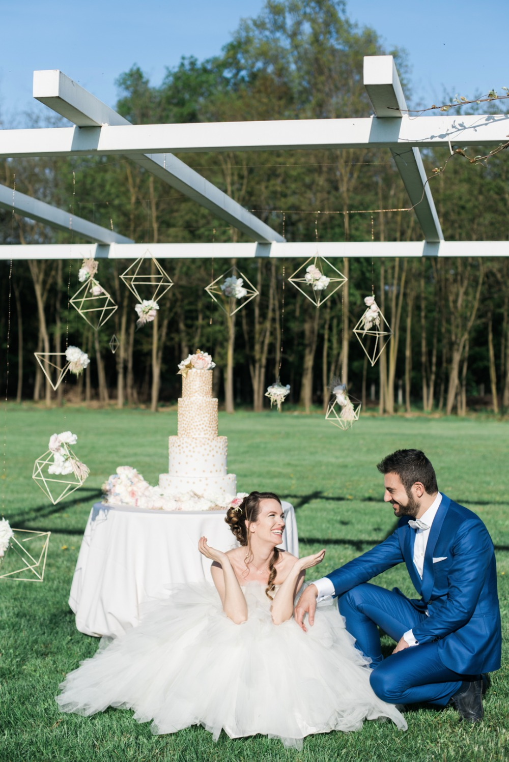 outdoor wedding cake display with hanging geometric backdrop