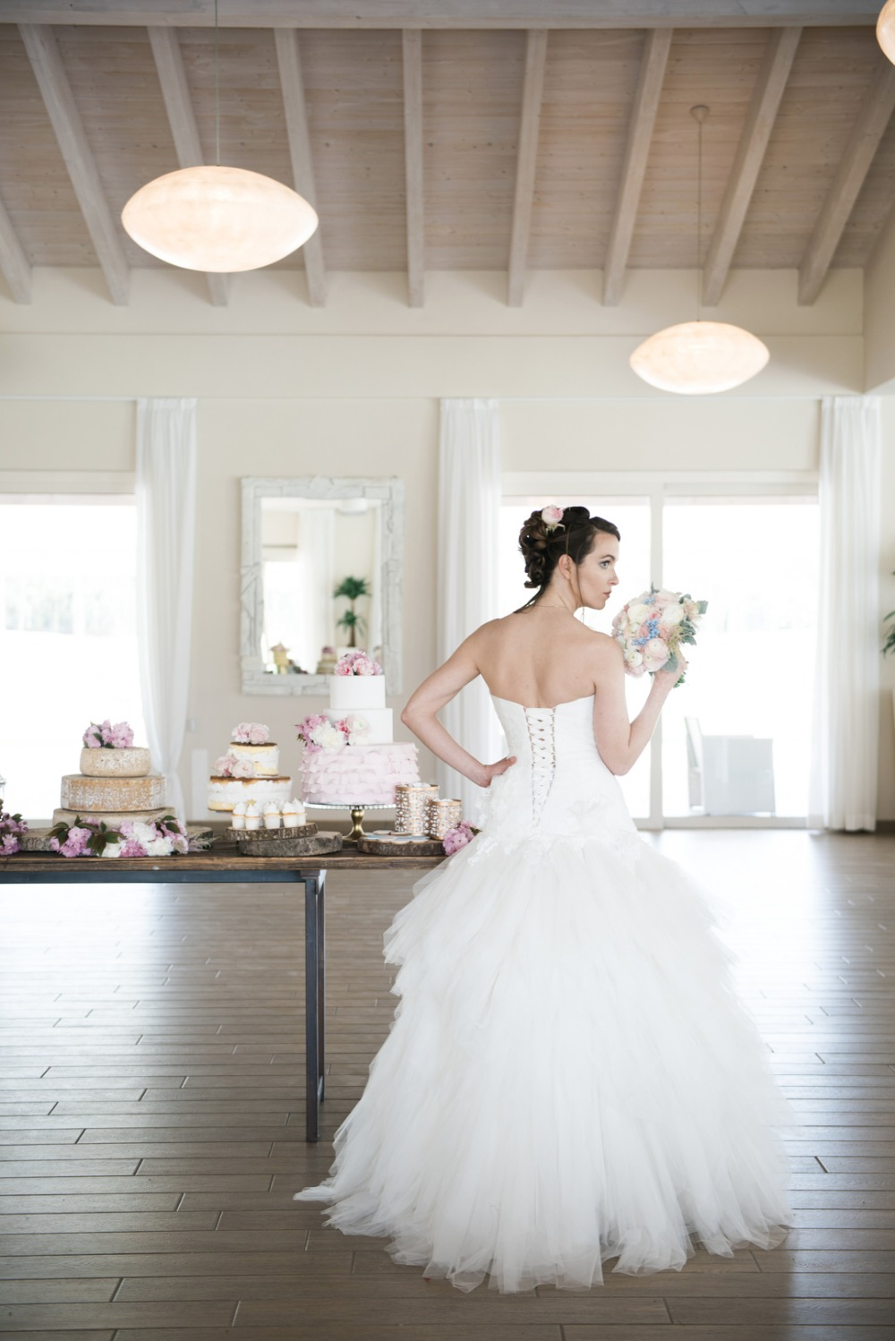 bride and several wedding cakes