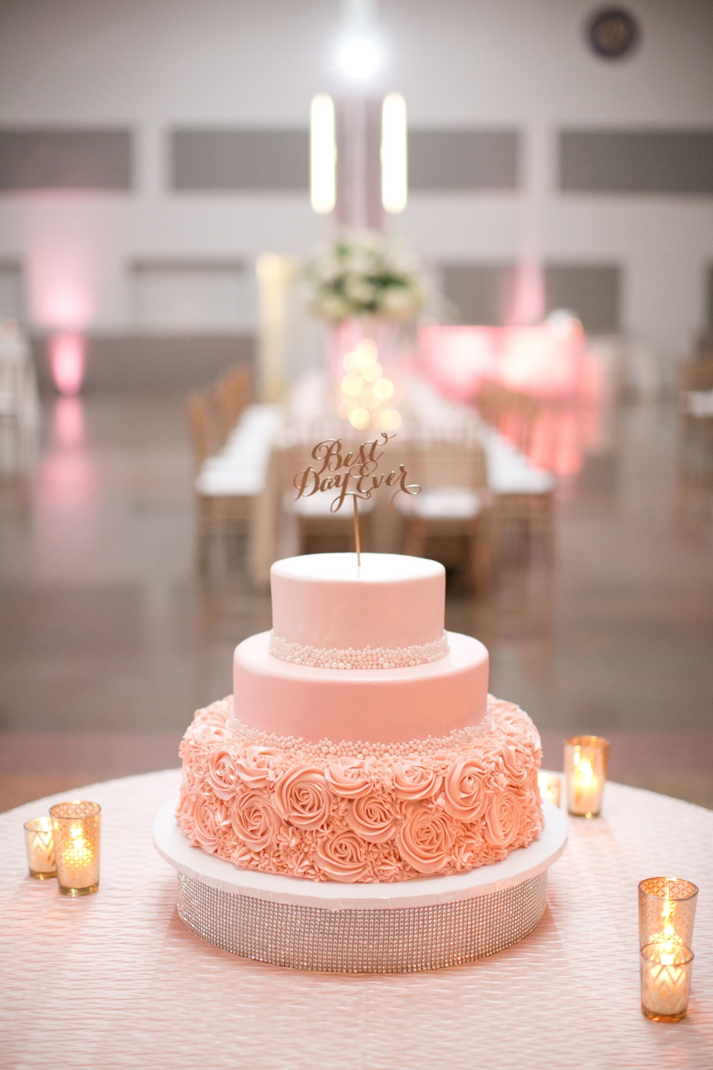 Pink wedding cake with gold topper