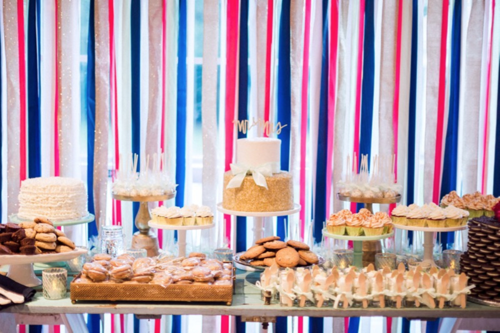 dessert table with streamer backdrop