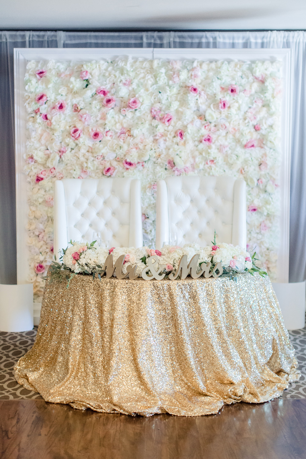 wedding sweetheart table with flower backdrop