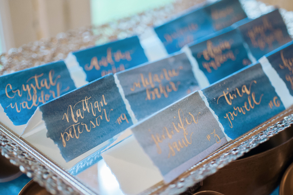 blue watercolor escort cards with gold script names