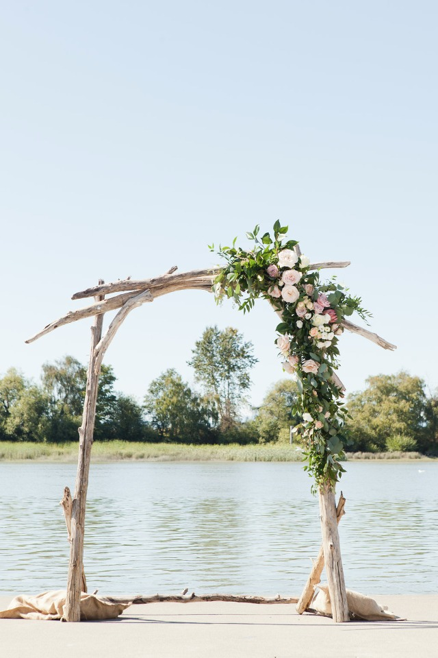driftwood wedding arch with asymmetrical flower accent