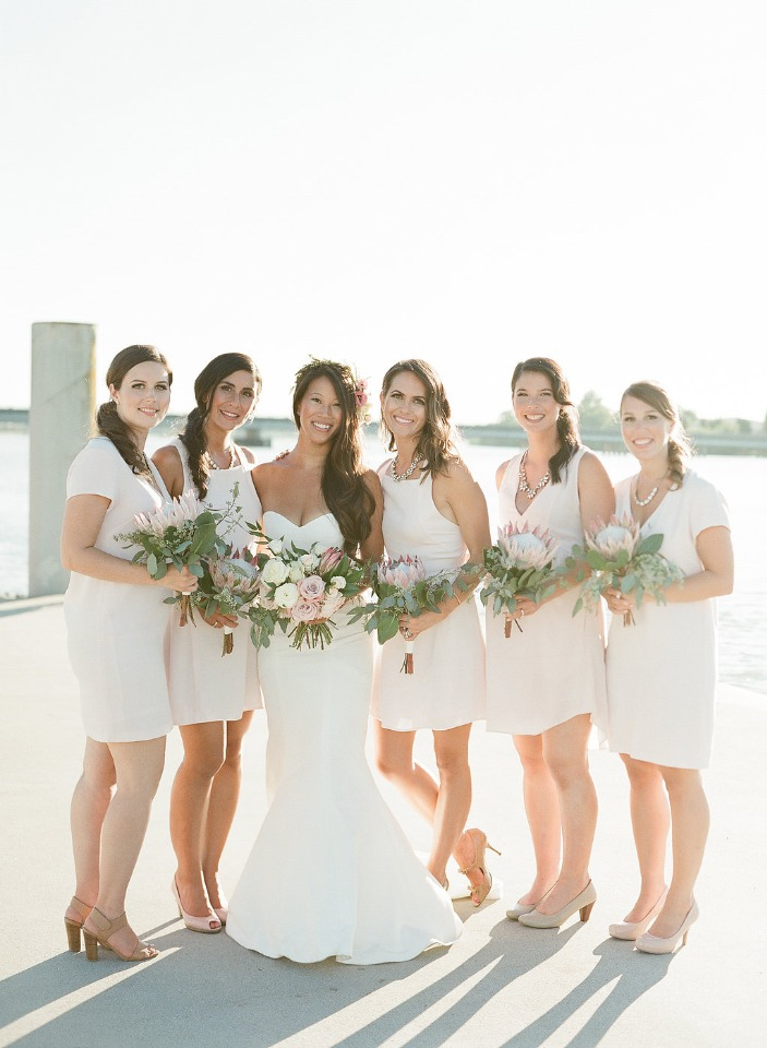 bridesmaids in varied styles of knee length white dresses