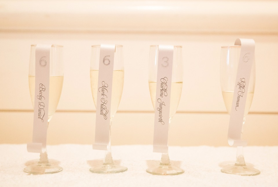 reception escort cards hanging off of a glass of champagne