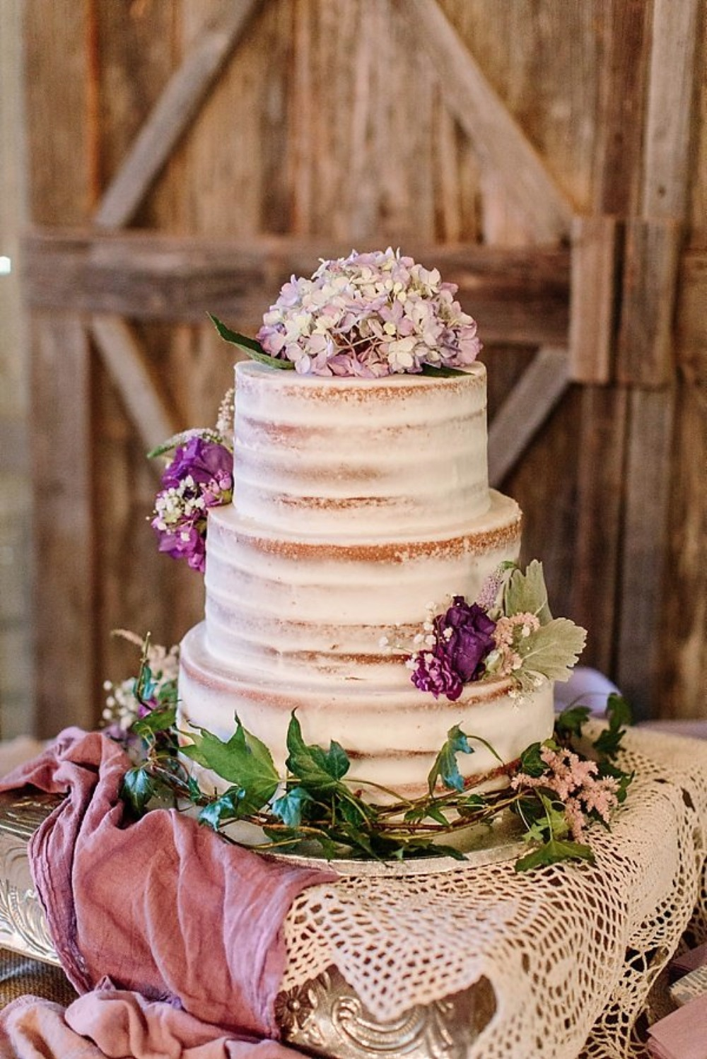 nearly naked wedding cake with purple flower topper