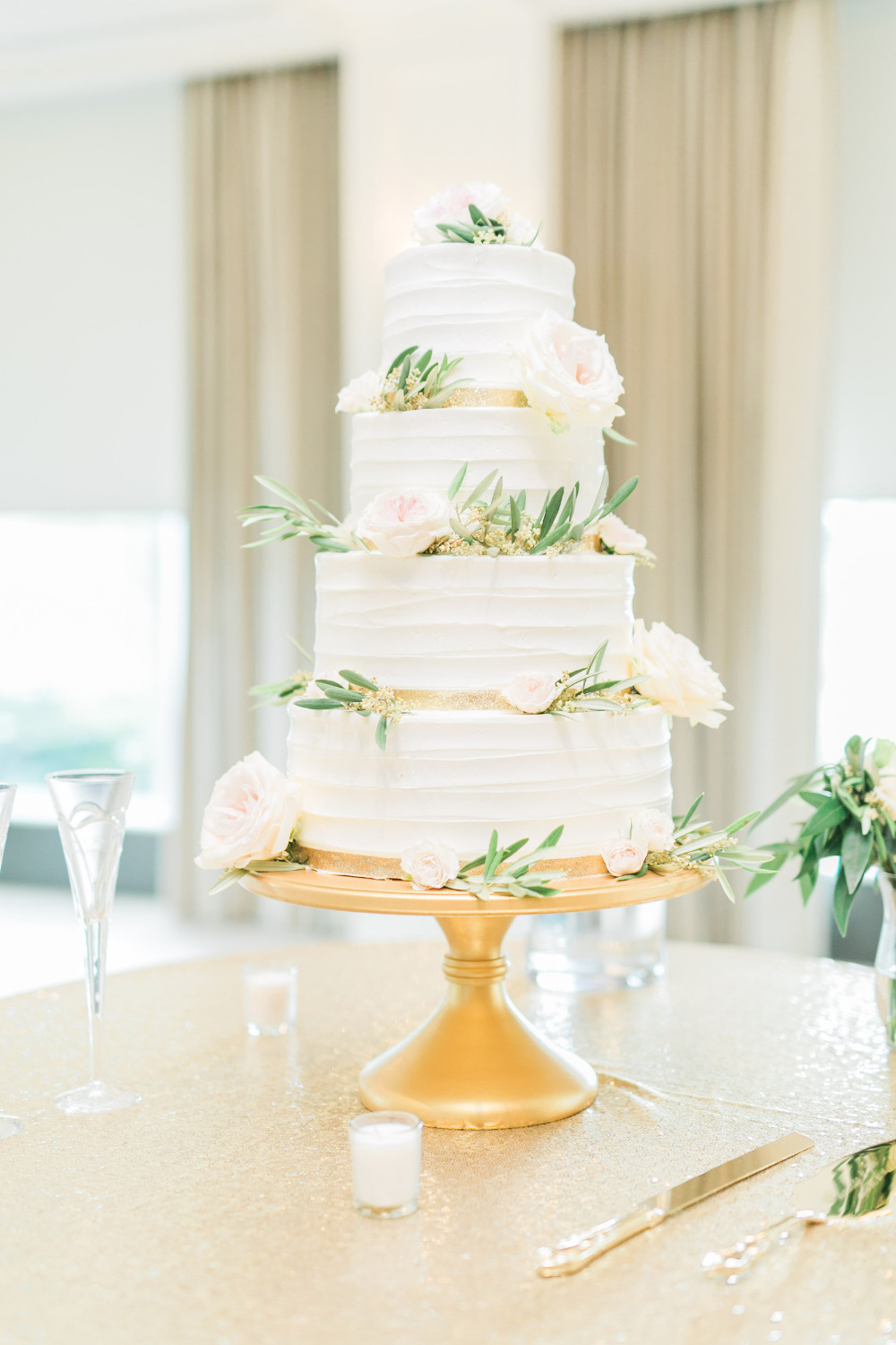 white wedding cake with gold ribbon