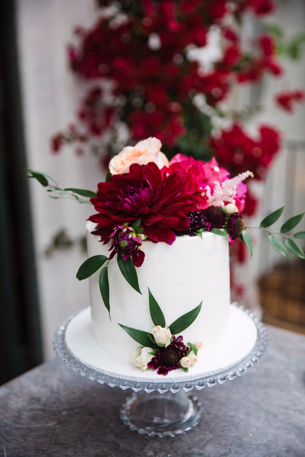 Sweetheart wedding cake with red, pink and peach florals