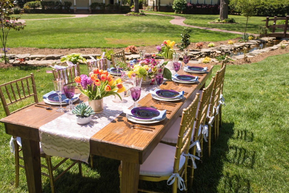 farm table with bright floral centerpieces and vintage china