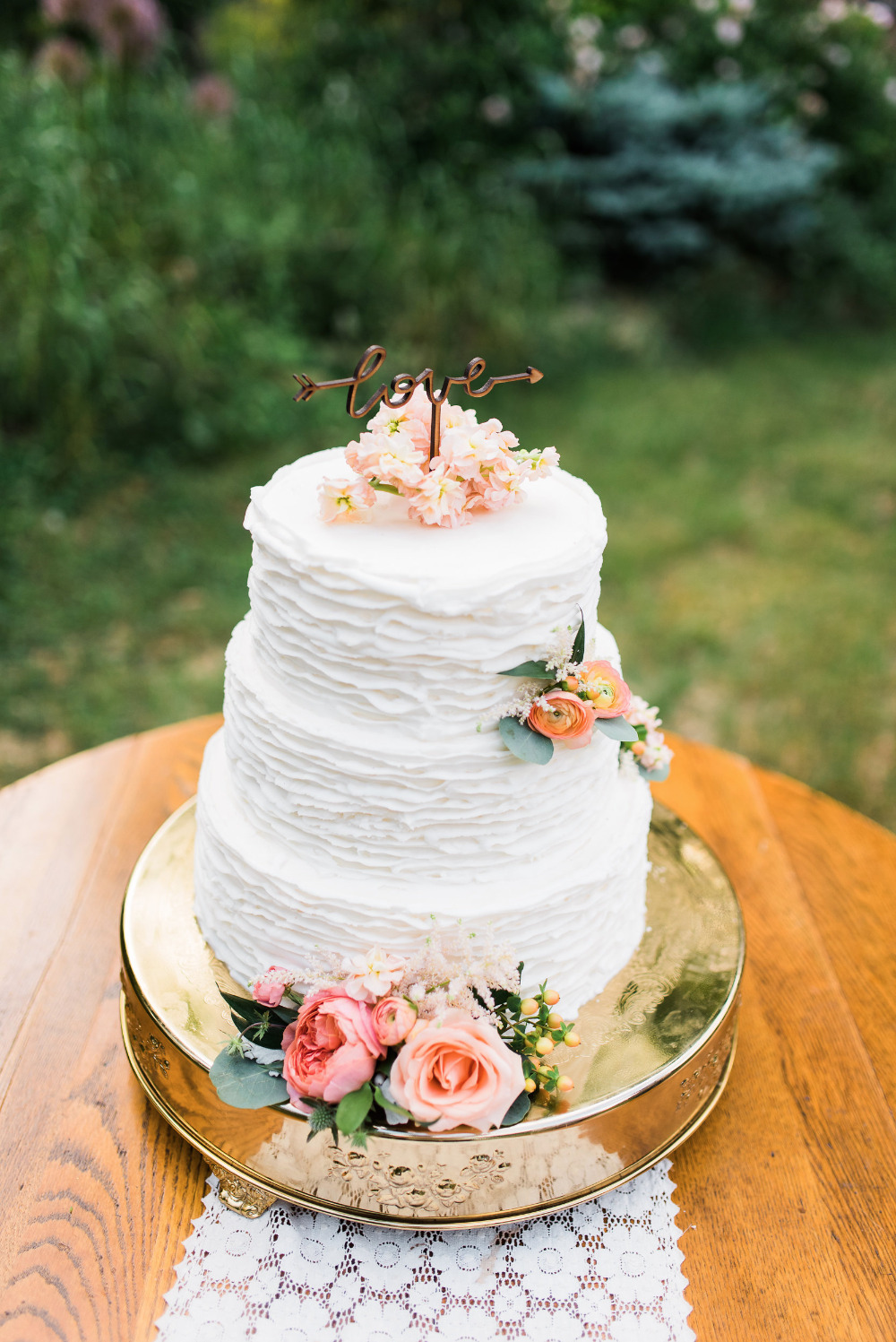 ruffled wedding cake with love topper