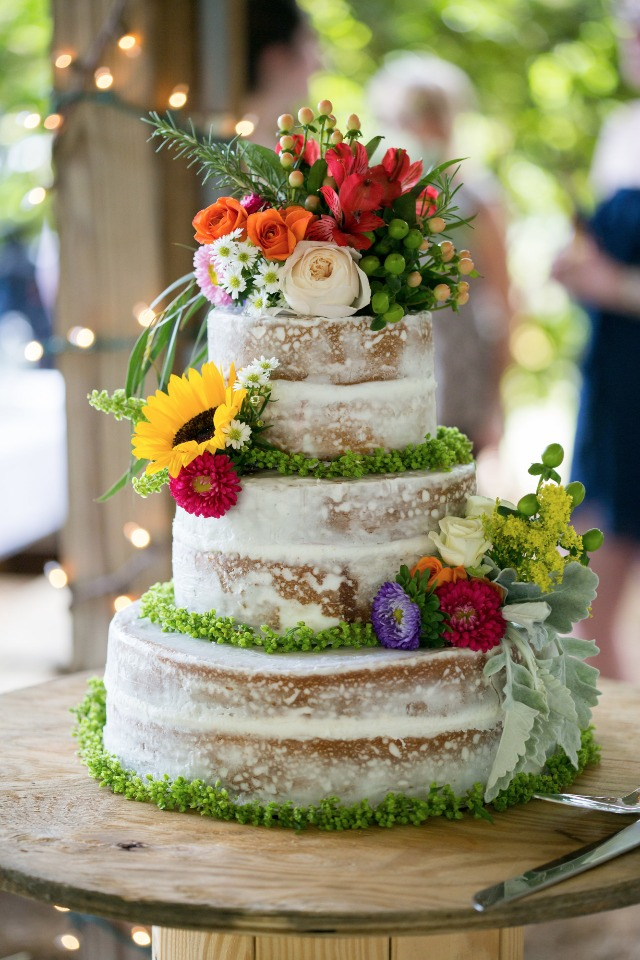 flower topped nearly naked wedding cake