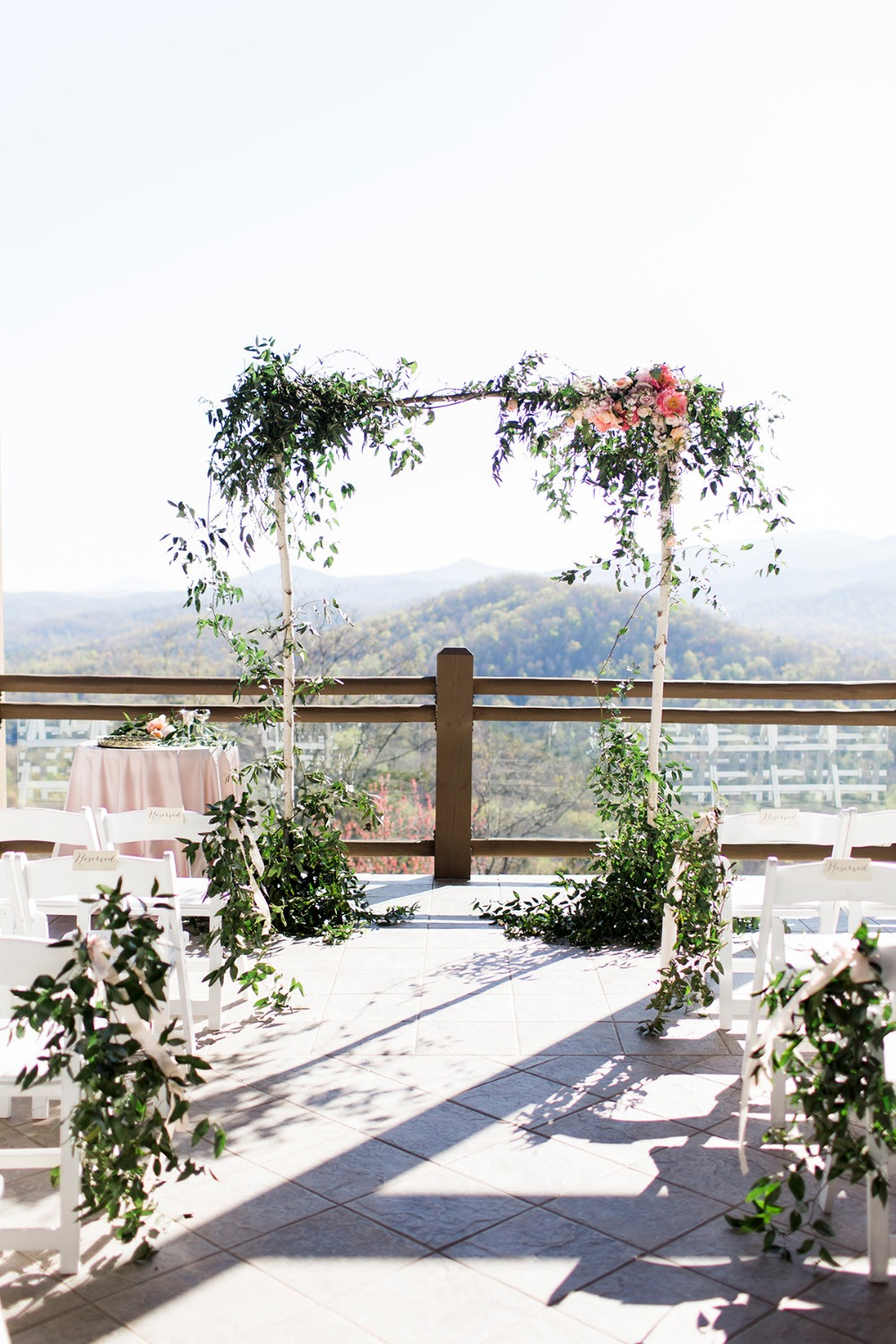 Birch wedding arbor with floral and leafy green details