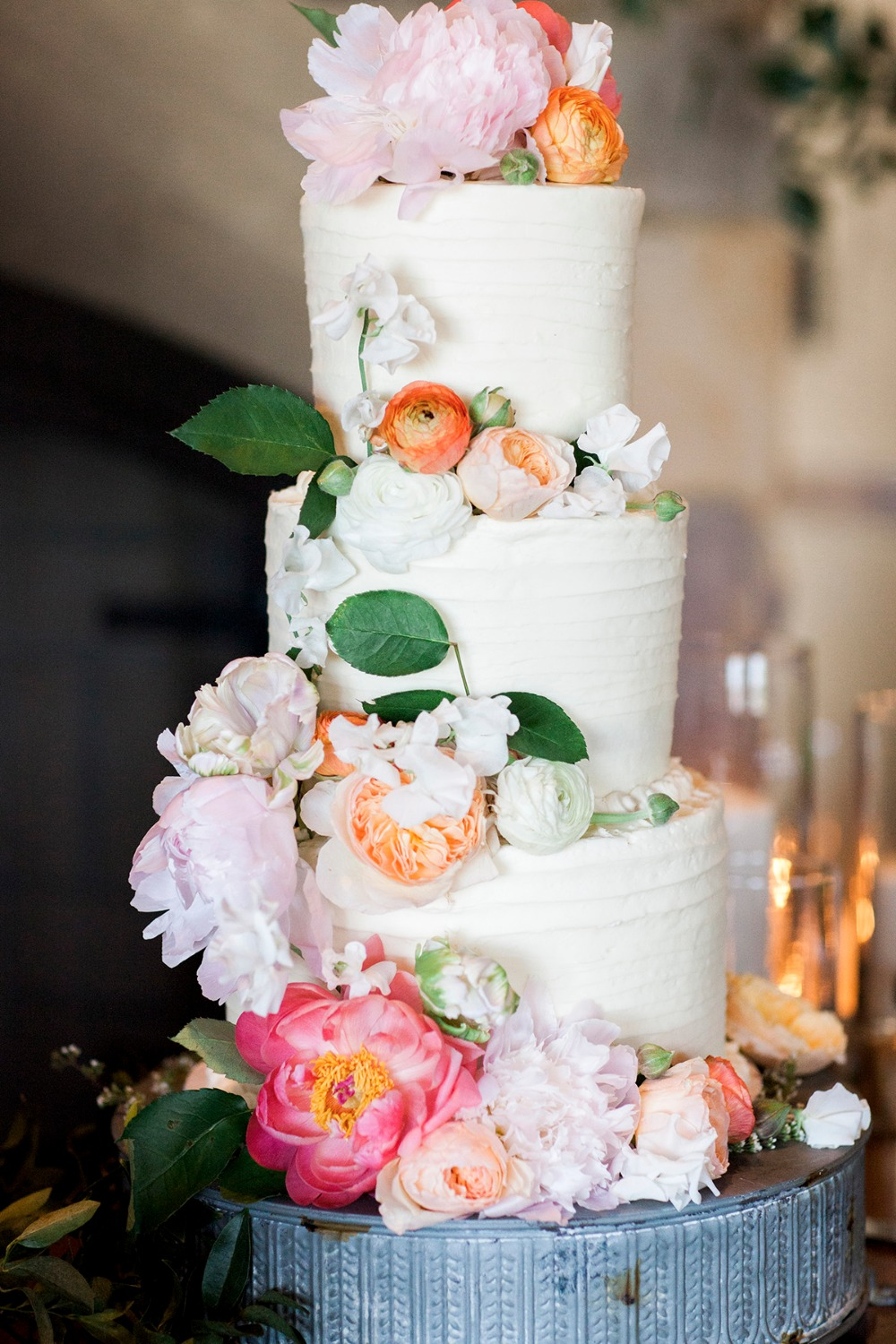 Three-tier wedding cake with cascading florals