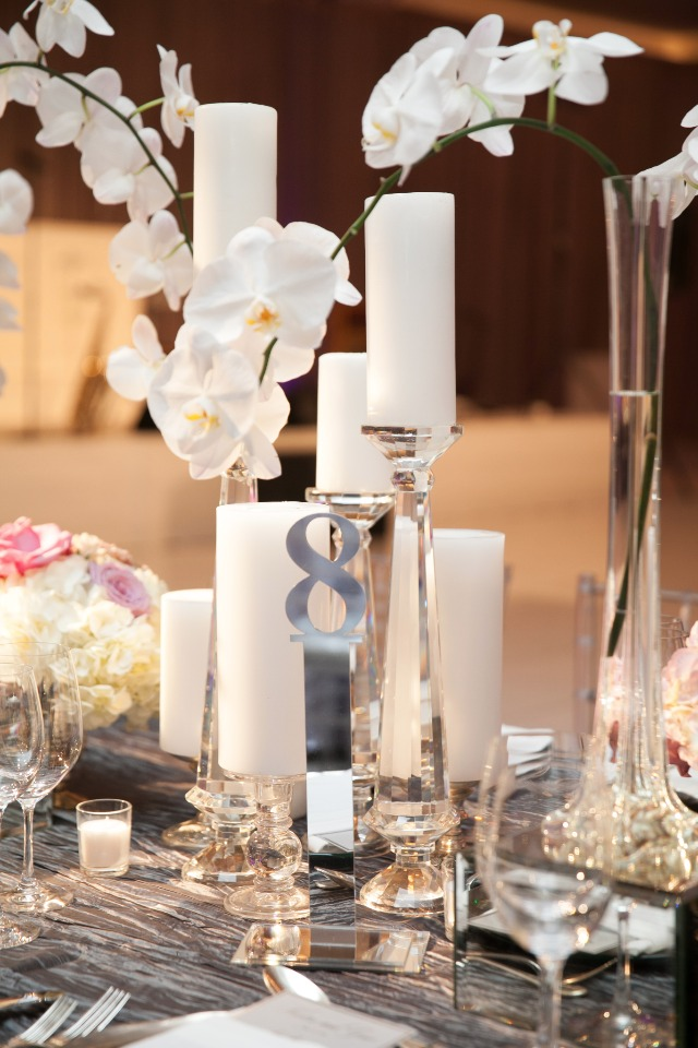 silver table number and orchid and candle centerpiece