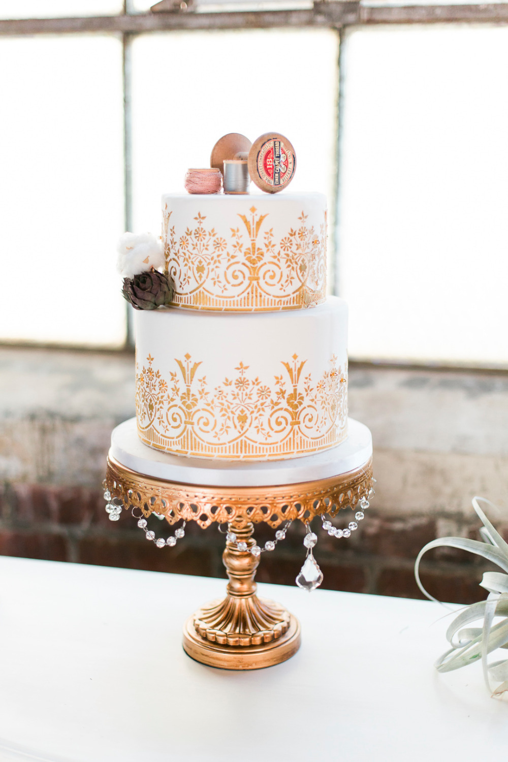gold and white wedding cake with thread spools
