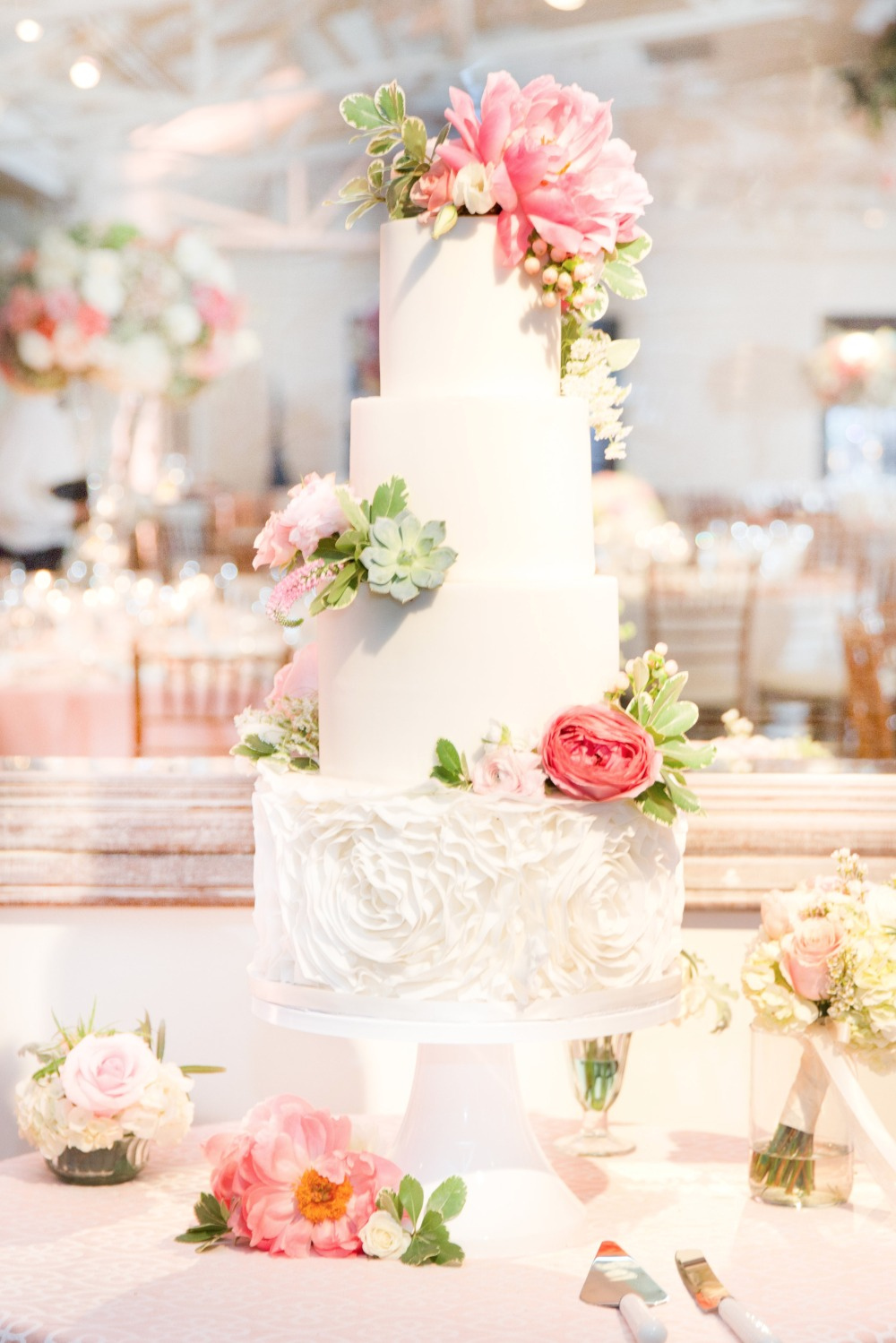 Four tier white wedding cake with florals