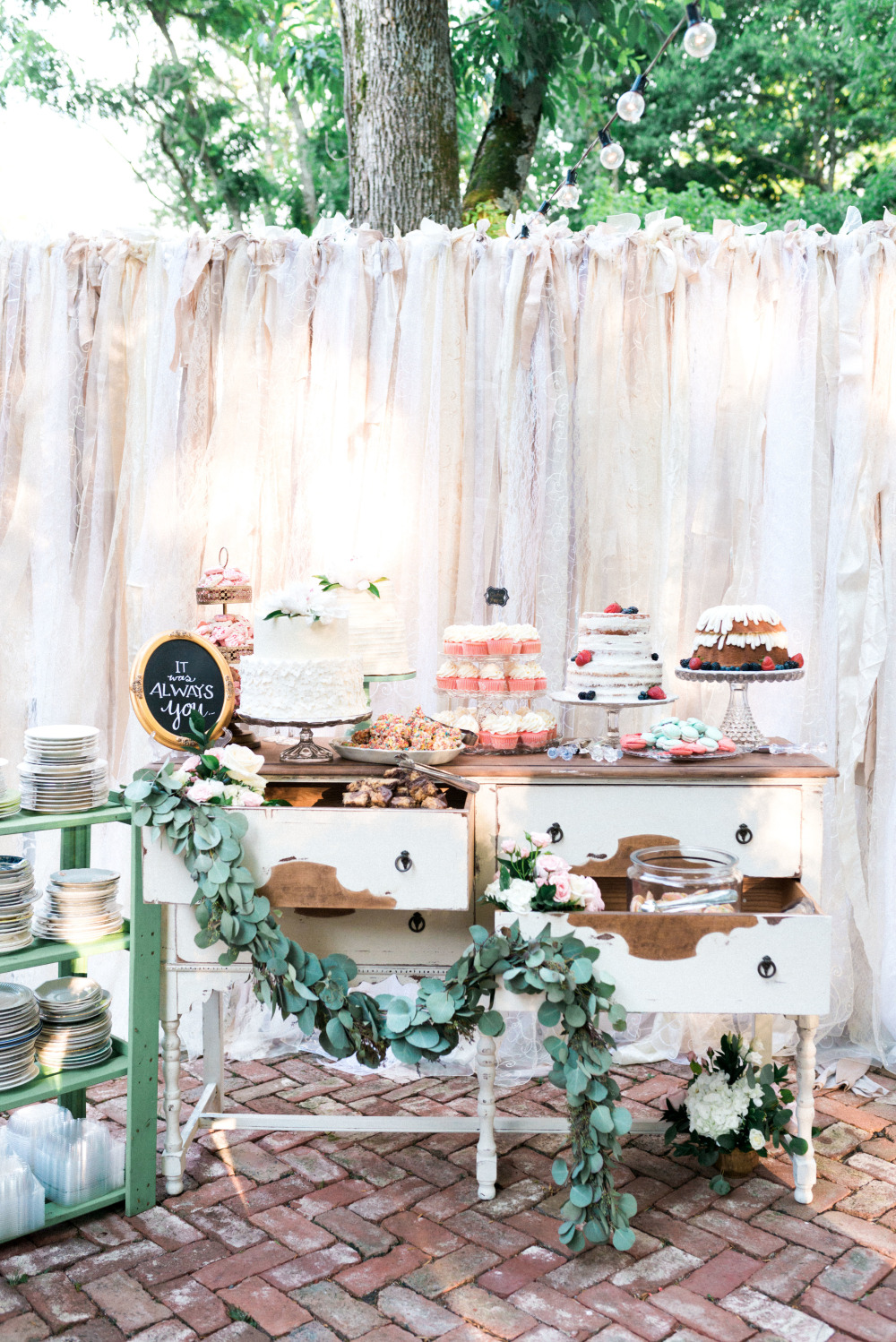 wedding dessert table with ribbon garland backdrop