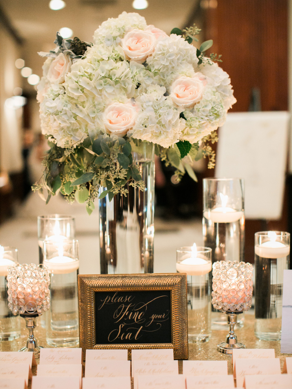 candle and floral decorated escort card table