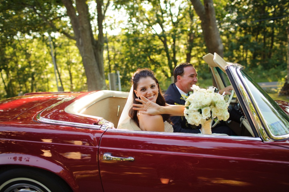bride and groom ride off in a cherry red classic convertable