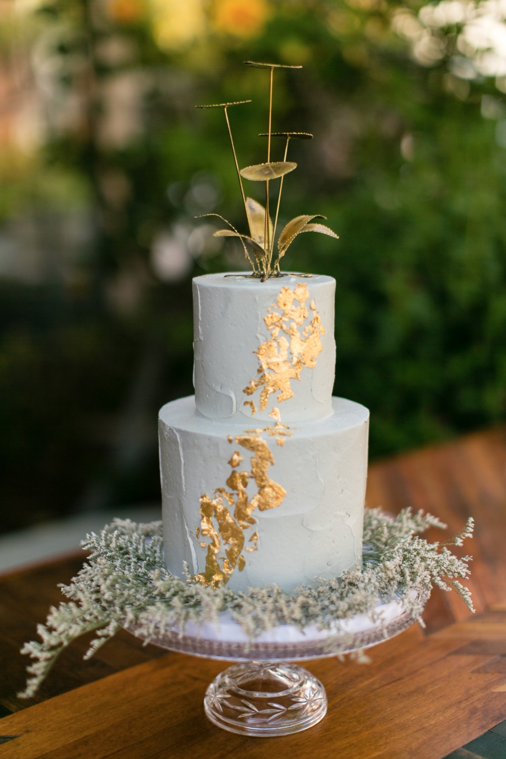 White and gold foil cake with gold metal topper