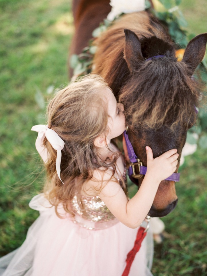 cute little flower girl loving this sweet little pony
