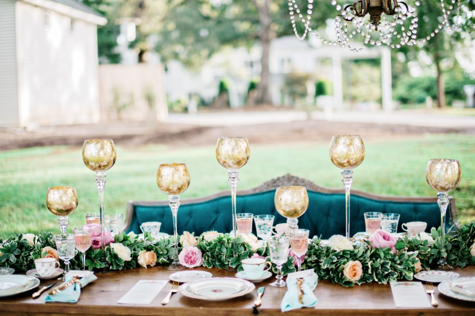 gilded glass goblets and floral runner decorate this glamorous wedding table