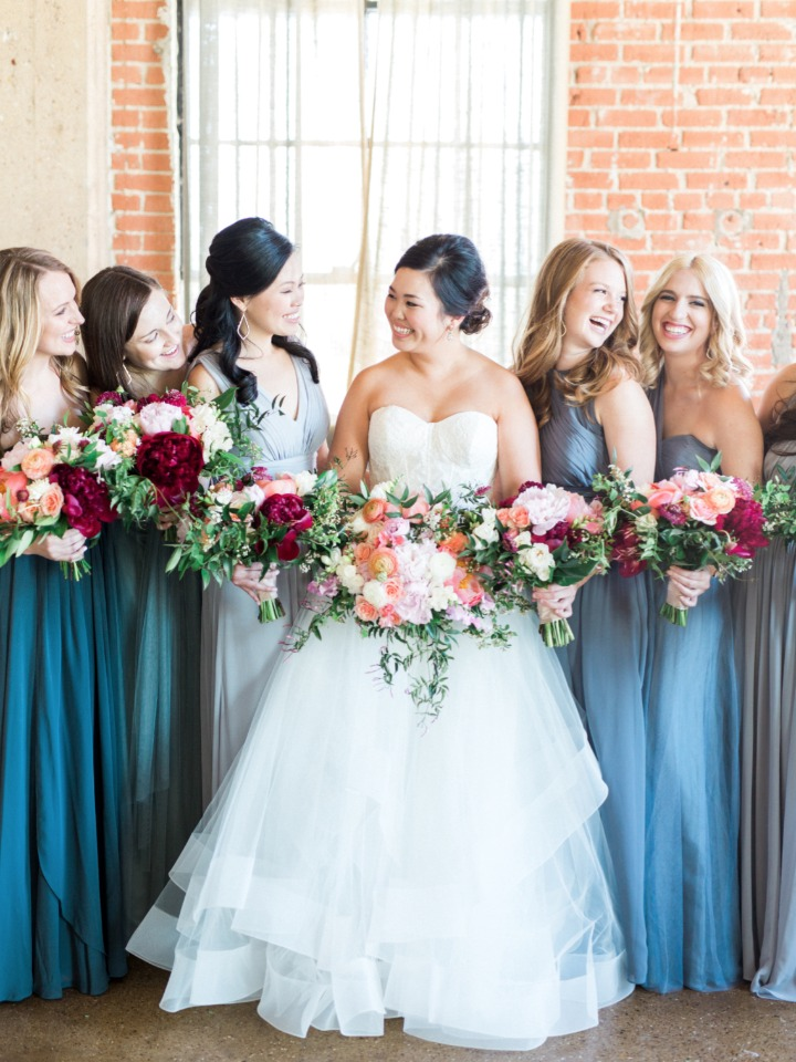 bridesmaids in assorted blue dresses with peach and deep red bouquets