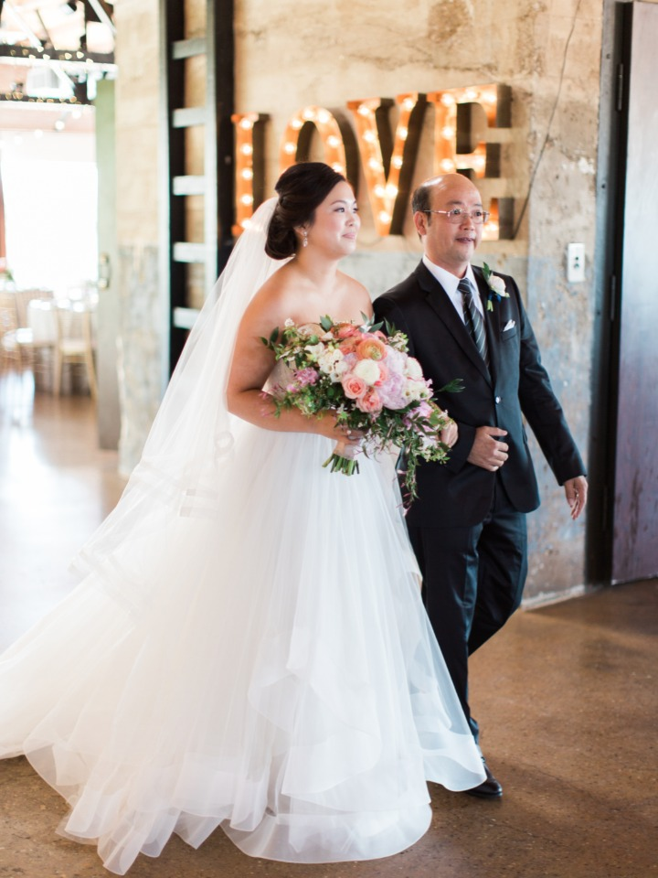 light up love marquee shines as the bride walks down the aisle