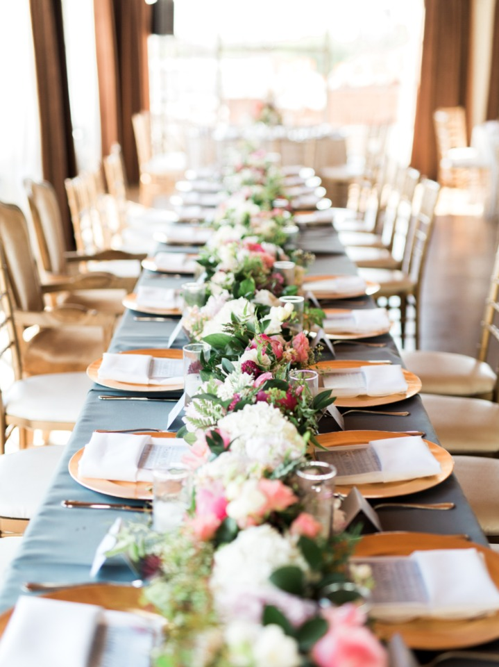 family style wedding seating with dusty blue linens and gold chargers