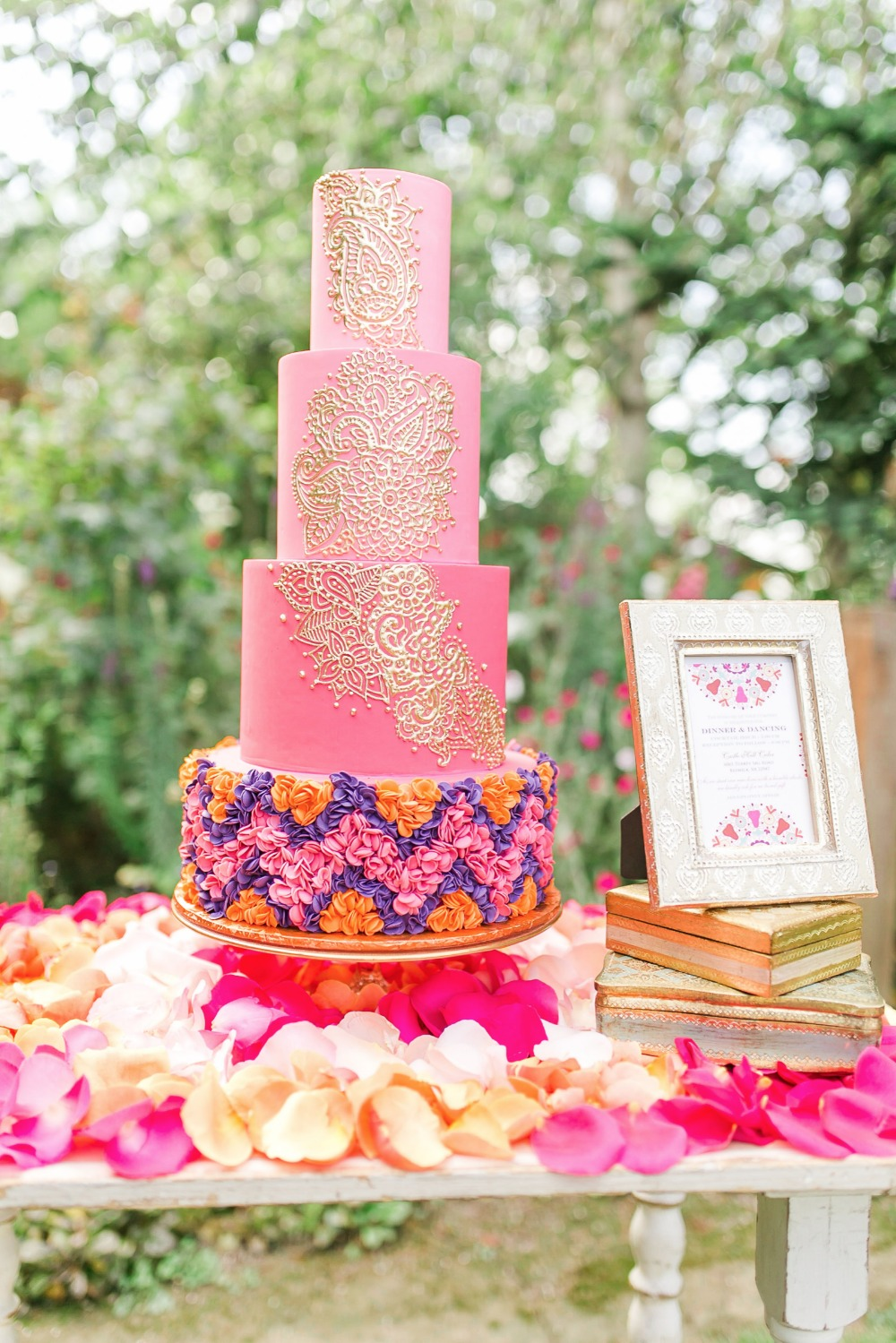 Grand four-tiered ombre fuchsia cake with intricate henna piping