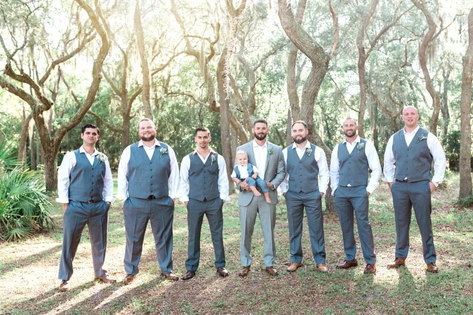 groomsmen in charcoal gray vests and slacks