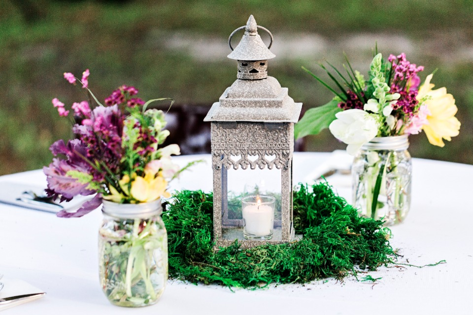 candle lit lantern table centerpiece with mason jar floral arrangements