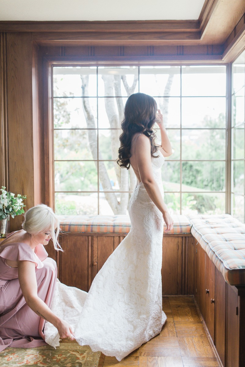 Bride in the final moments of prep her with maid of honor before her Santa Barbara Riviera wedding.