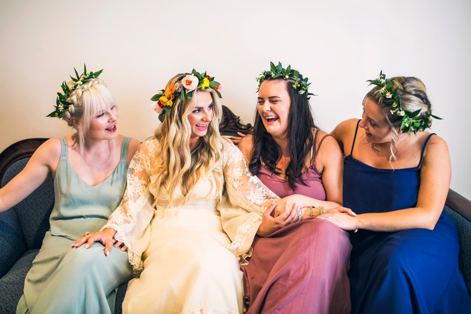bridesmaids in mismatched dresses and flower halos