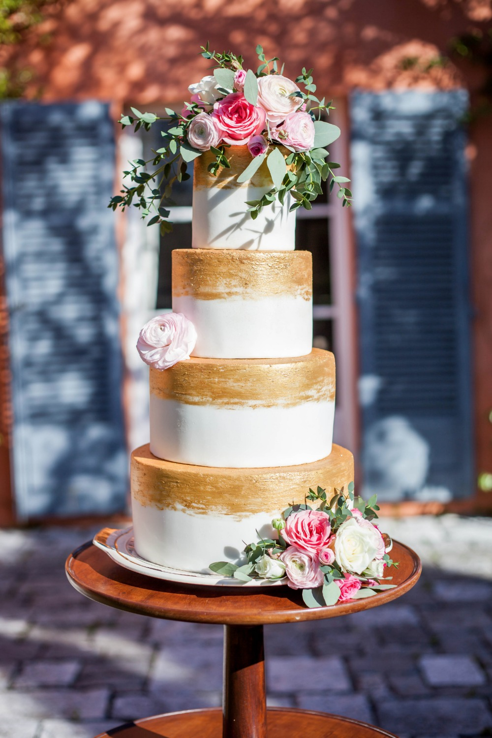 Gold and white wedding cake with pink roses